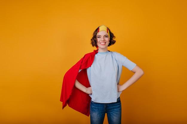 Lachendes brünettes mädchen im superhelden-outfit, das auf gelbem raum aufwirft