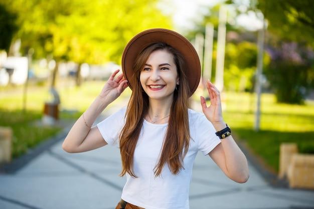 Lachendes brünettes mädchen mit blasser haut, das trendige kleidung trägt und in einem park steht und einen sonnigen morgen genießt. porträt einer exquisiten jungen dame mit hut und weißem t-shirt, die in der nähe einer parkgasse posiert.