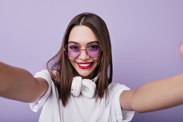 Lachendes brünettes mädchen mit weißen kopfhörern, die foto von sich machen. innenaufnahme der bezaubernden braunhaarigen frau in der sonnenbrille, die selfie macht.
