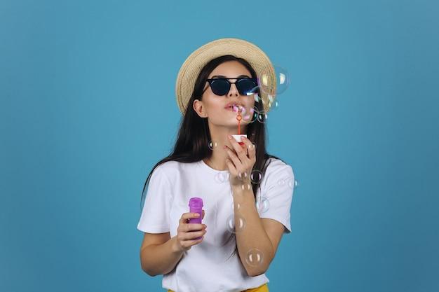 Lachendes brunettemädchen im sommerhut und -sonnenbrille hat spaß mit seifenballonen
