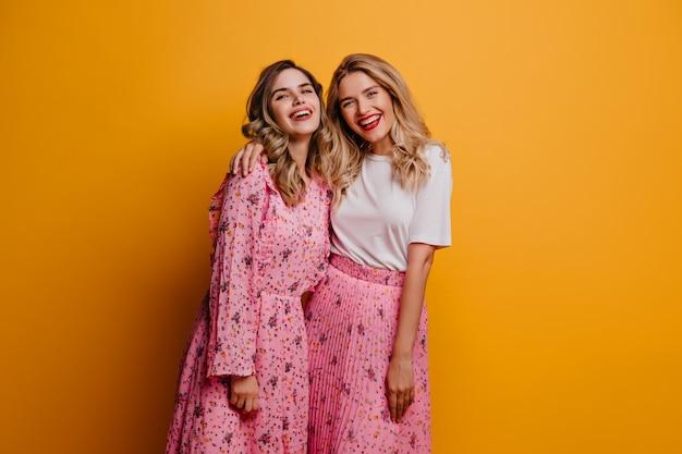 Lachendes entzückendes mädchen, das freizeit mit ihrer schwester genießt. schöne debonair dame im rosa rock, der mit bestem freund aufwirft.