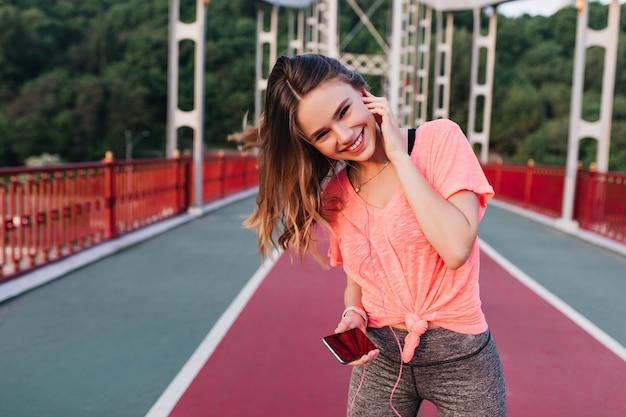 Lachendes europäisches mädchen mit smartphone, das mit vergnügen am stadion aufwirft. erstaunliches weibliches modell, das frühlingstag im freien verbringt und übungen macht.