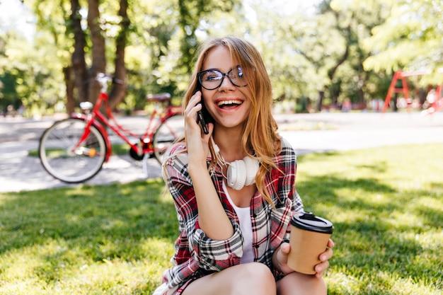Lachendes freudiges mädchen, das im park am telefon spricht. debonair europäische frau in den gläsern, die freund im sommertag anrufen.
