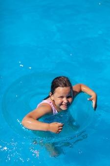 Lachendes glückliches mädchen lernt auf einem transparenten blauen aufblasbaren kreis in einem schwimmbecken zu schwimmen.