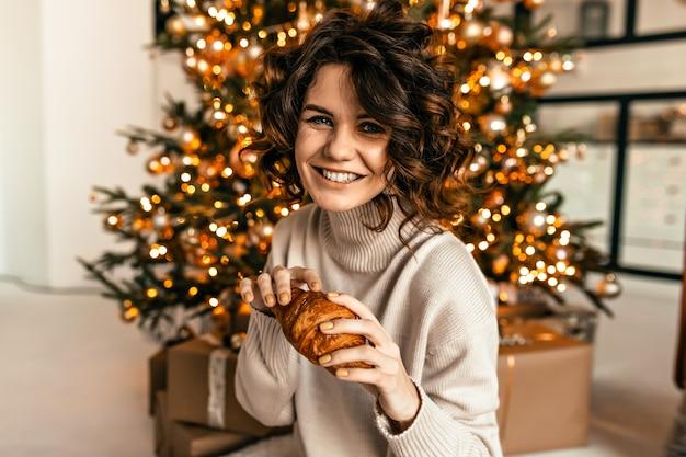 Lachendes glückliches mädchen mit lockiger frisur, die mit croissant über weihnachtsbaum mit glücklichen gefühlen aufwirft. neujahrsmorgen, weihnachtsfeier