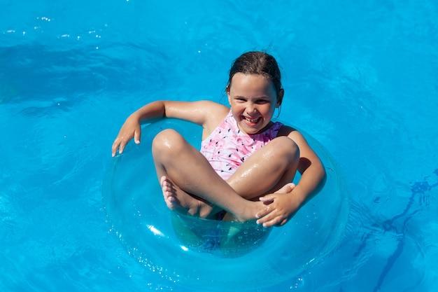 Lachendes glückliches mädchen schwimmt im schneidersitz auf einem blauen aufblasbaren kreis am meer oder im pool glücklich...