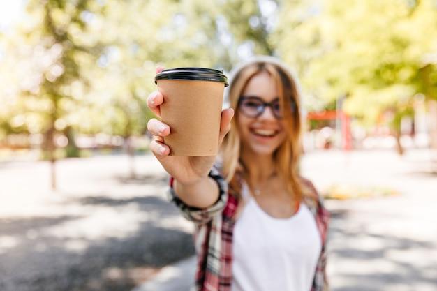Lachendes herrliches mädchen, das latte im park trinkt. unscharfes porträt der blonden frau mit tasse kaffee auf vordergrund.