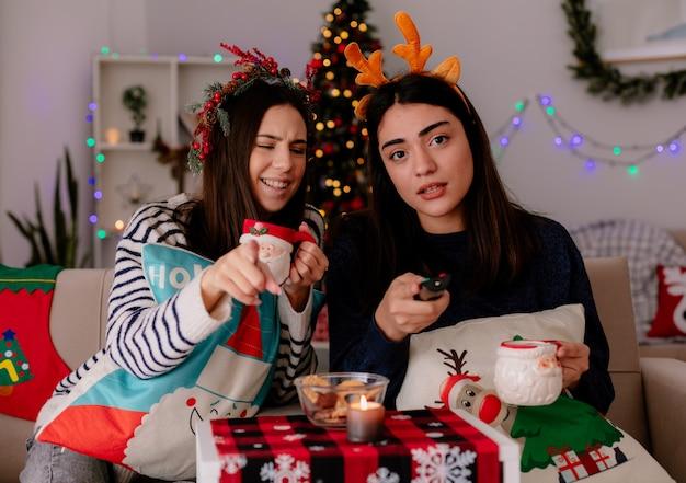 Lachendes hübsches junges mädchen mit stechpalmenkranz hält tasse und punkte, die auf einem sessel sitzen, während ihre freundin eine tv-fernbedienung hält und die weihnachtszeit zu hause genießt