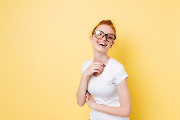 Lachendes ingwermädchen in den brillen, die die kamera betrachten