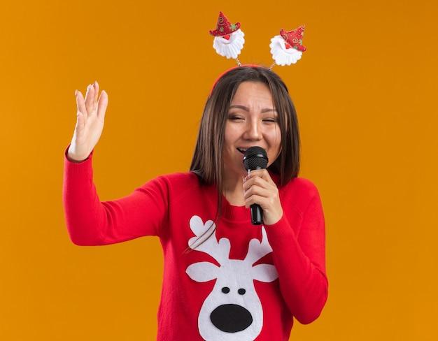 Lachendes junges asiatisches mädchen, das weihnachtshaarbügel mit pullover trägt, spricht auf mikrofon lokalisiert auf orange wand