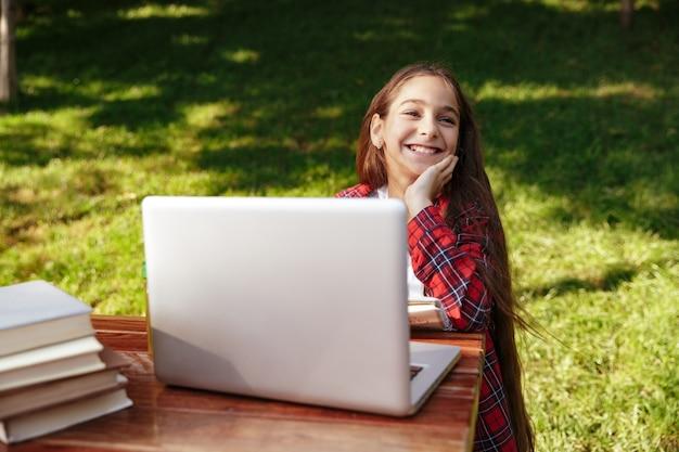 Lachendes junges brünettes mädchen, das mit laptop am tisch sitzt