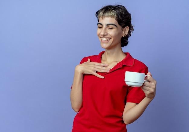 Lachendes junges kaukasisches mädchen mit pixie-haarschnitt, der tasse hält hand auf brust mit geschlossenen augen lokalisiert auf lila hintergrund mit kopienraum