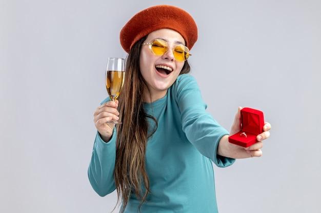 Lachendes junges mädchen am valentinstag mit hut mit brille, das ein glas champagner mit ehering auf weißem hintergrund hält