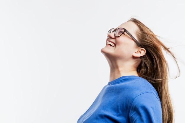 Lachendes junges mädchen mit brille in einem blauen t-shirt