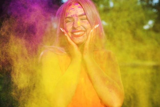 Lachendes junges model posiert mit explodierender gelber farbe beim sommer-holi-festival