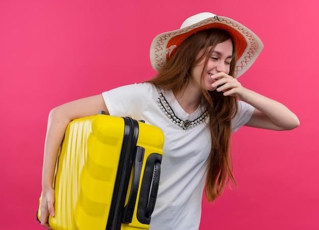 Lachendes junges reisendes mädchen, das hut hält, der koffer hält und hand nahe mund auf lokalisierten rosa raum setzt