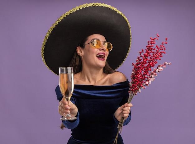 Lachendes junges schönes mädchen, das blaues kleid und brille mit sombrero hält ebereschenzweig mit glas champagner lokalisiert auf lila hintergrund trägt