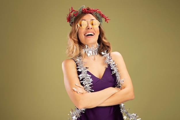 Lachendes junges schönes mädchen, das lila kleid und brille mit kranz und girlande am hals trägt, die die hände einzeln auf olivgrünem hintergrund kreuzt