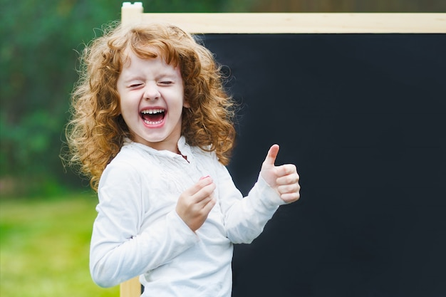 Lachendes kind, das sich gestikulierte daumen zeigt