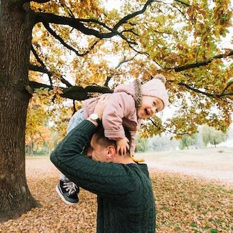 Lachendes kind und vati, die im herbstpark spielen
