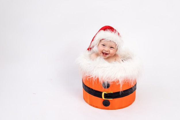 Lachendes kleines baby, das in der weihnachtsmütze im korb auf weißem lokalisiertem hintergrund sitzt