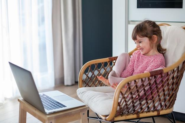 Lachendes kleines mädchen im video-chat mit ihren großeltern am laptop