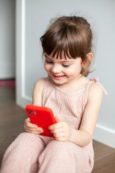 Lachendes kleines mädchen mit handy, das auf einem boden sitzt. sie spielt spiele oder schaut sich cartoons auf dem smartphone an. konzept der digitalen generation und der telefonsucht.