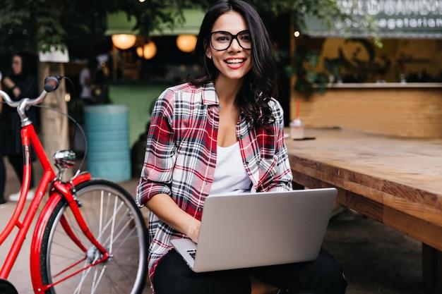 Lachendes lateinamerikanisches schwarzhaariges mädchen, das mit fahrrad und laptop aufwirft. glückliche stilvolle dame mit computer, der auf der straße sitzt.