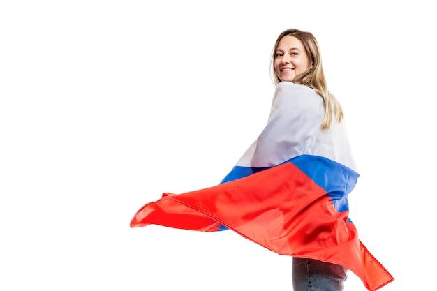 Lachendes mädchen, das eine russische flagge hält. unabhängigkeitstag und patriotismus feiern. . platz für text.