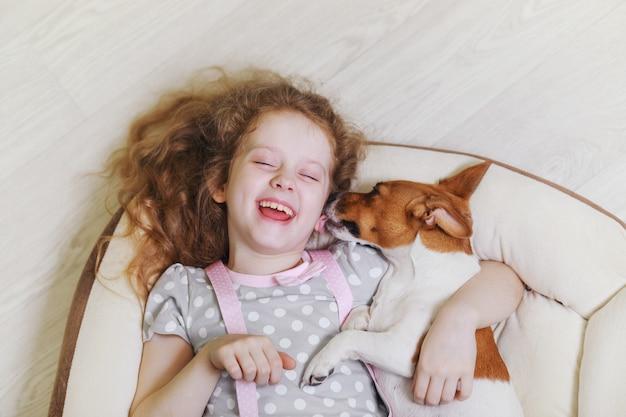 Lachendes mädchen, das einen hund, liegend auf hölzernem hintergrund umarmt und küsst.