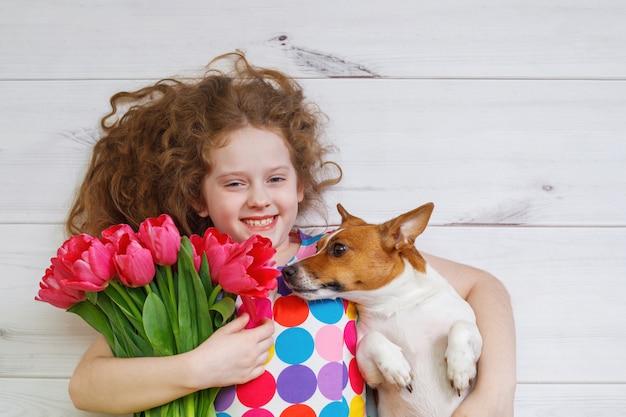 Lachendes mädchen, das einen welpen umarmt und rote tulpen hält.