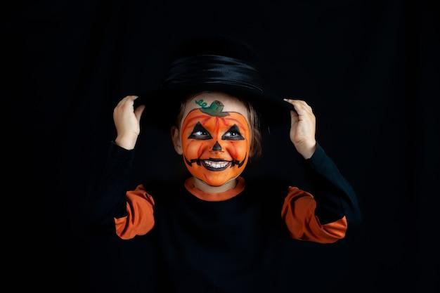 Lachendes mädchen im kürbis-make-up für halloween hält einen schwarzen hut auf ihrem kopf.