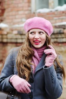 Lachendes mädchen in grauem mantel und rosa baskenmütze