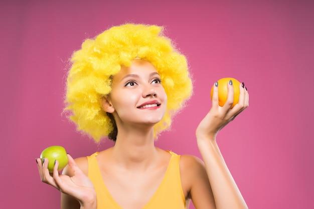 Lachendes mädchen in leuchtend orangefarbener perücke auf rosa hintergrund hält äpfel in den händen