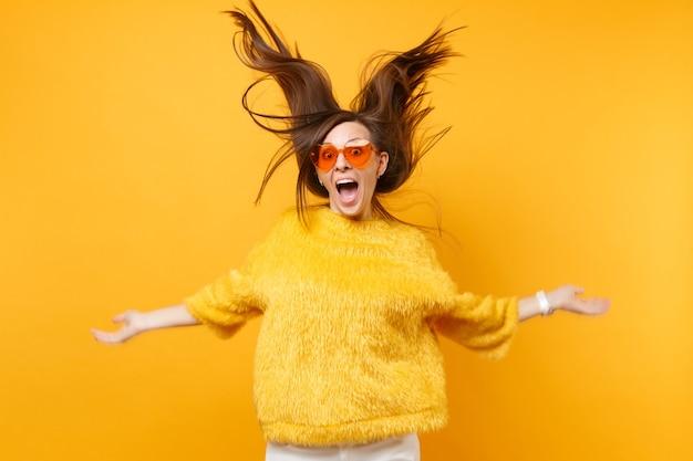Lachendes mädchen in pelzpullover und herzorangefarbener brille, die im studio herumalbern, mit volantem haar einzeln auf hellgelbem hintergrund. menschen aufrichtige emotionen, lifestyle-konzept. werbefläche.