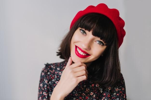 Lachendes mädchen mit kurzer frisur und trendigem französischem outfit, das das aufstellen ihres kinns auf unscharfem hintergrund aufwirft. nahaufnahmeporträt der lächelnden jungen brünetten frau in den weinlesekleidern, die mit bewunderung suchen