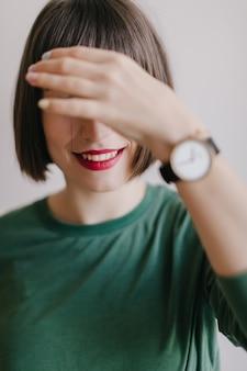Lachendes mädchen mit roten lippen bedeckt ihre augen. innenfoto des angenehmen weiblichen modells in der trendigen armbanduhr, die aufwirft.