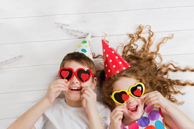 Lachendes mädchen und junge mit sonnenbrille, halten kerzenherzform