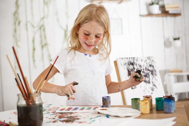 Lachendes mädchen voller freude mit händen in farbe im kunstraum. fröhliches kind, das bild mit lächeln zeichnet. erfreutes kind strahlt positive emotionen und glück aus.