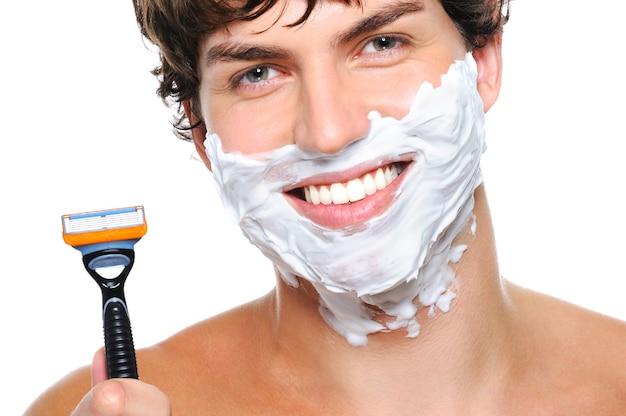 Lachendes männergesicht mit rasierschaum und rasiermesser in der nähe des gesichts