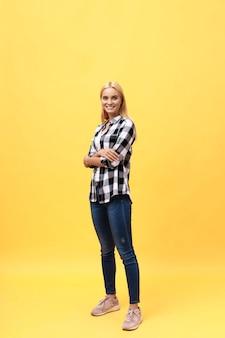 Lachendes modell in voller länge im studio. blick in die kamera. isolierten gelben hintergrund
