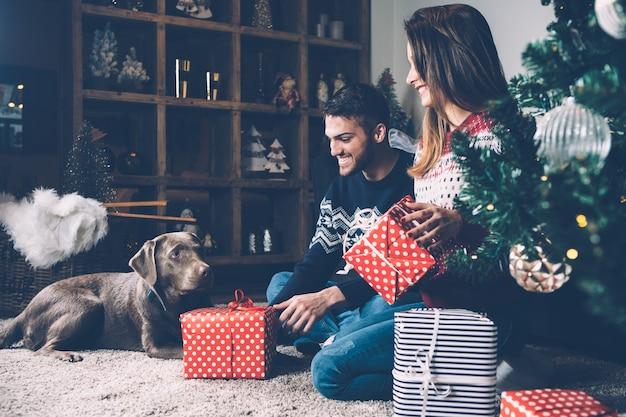 Lachendes paar mit geschenken und hund