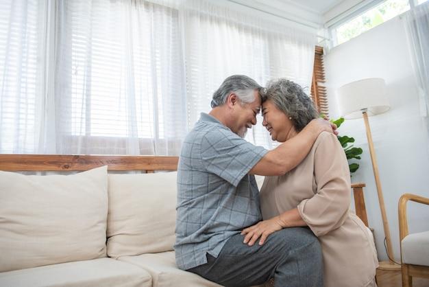 Lachendes rentner hübsches asiatisches paar, das zu hause auf der couch sitzt, ehepartner, die offenes gesundes zahniges lächeln haben, zahnärztliche kontrolluntersuchungen für alte leute, krankenversicherungs-gesundheitskonzept