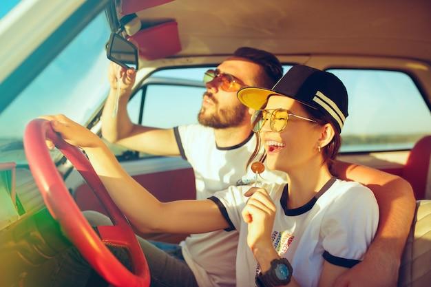 Lachendes romantisches paar, das im auto sitzt, während auf einem roadtrip am sommertag