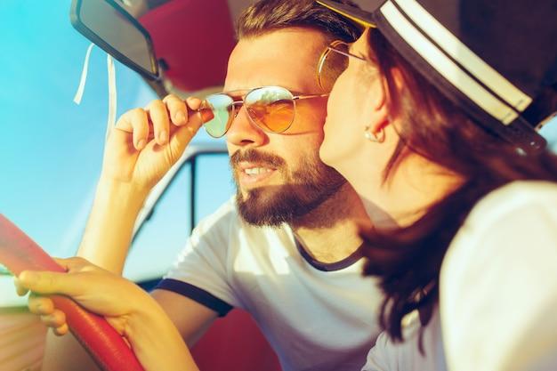 Lachendes romantisches paar, das im auto sitzt, während es unterwegs ist
