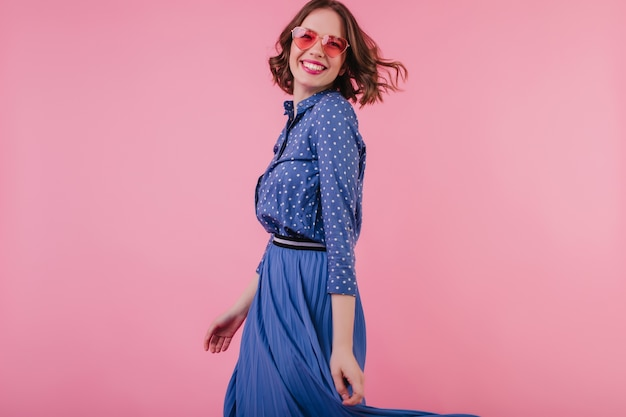 Lachendes sorgloses mädchen im midirock, das innen-fotoshooting genießt. europäisches weibliches modell in der stilvollen bluse und in der sonnenbrille, die auf rosa wand stehen.