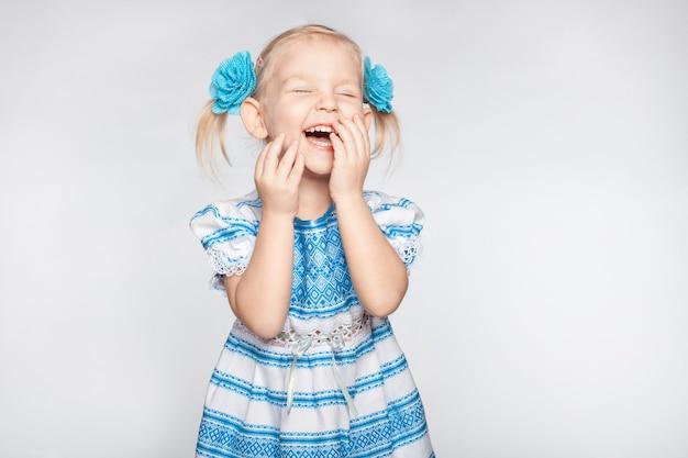 Lachendes süßes kleines mädchen auf weiß
