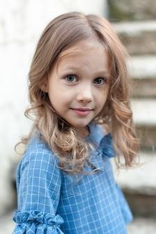 Lachendes süßes mädchenporträt zu hause. kleines kind, das kamera lächelt und betrachtet.