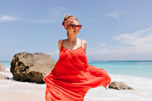 Lachendes weißes mädchen, das am sonnigen wochenende am strand herumalbert. foto im freien der kaukasischen romantischen dame im trendigen kleid, das mit steinen tanzt.