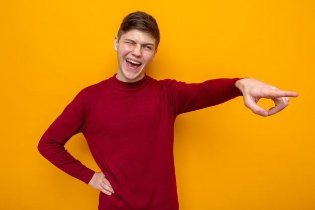 Lachpunkte an der seite junger gutaussehender kerl mit rotem pullover